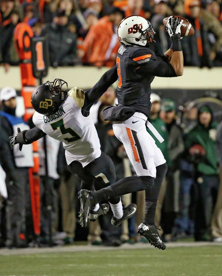 Oklahoma State wide receiver Marcell Ateman (3) grabs a pass in front of Baylor cornerback Demetri Goodson (3) in the first quarter of an NCAA college football game in Stillwater, Okla., Saturday, Nov. 23, 2013. (AP Photo/Sue Ogrocki) Photo: Sue Ogrocki, Associated Press / AP