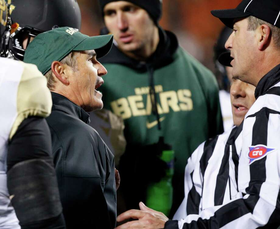 Baylor head coach Art Briles, left, talks with two officials in the second quarter of an NCAA college football game against Oklahoma State in Stillwater, Okla., Saturday, Nov. 23, 2013. (AP Photo/Sue Ogrocki) Photo: Sue Ogrocki, Associated Press / AP
