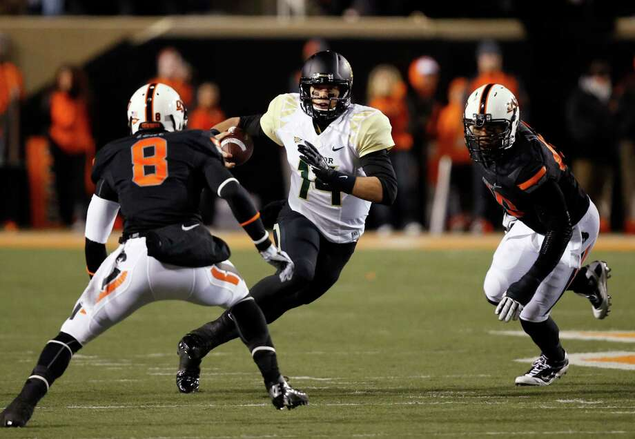 Baylor quarterback Bryce Petty (14) carries past Oklahoma State safety Daytawion Lowe (8) and defensive end Tyler Johnson (40) in the first quarter of an NCAA college football game in Stillwater, Okla., Saturday, Nov. 23, 2013. (AP Photo/Sue Ogrocki) Photo: Sue Ogrocki, Associated Press / AP