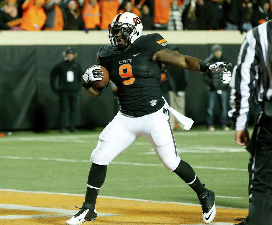 Oklahoma State fullback Kye Staley runs into the end zone for a touchdown against Baylor in the first quarter of an NCAA college football game in Stillwater, Okla., Saturday, Nov. 23, 2013. (AP Photo/Sue Ogrocki) Photo: Sue Ogrocki, Associated Press / AP