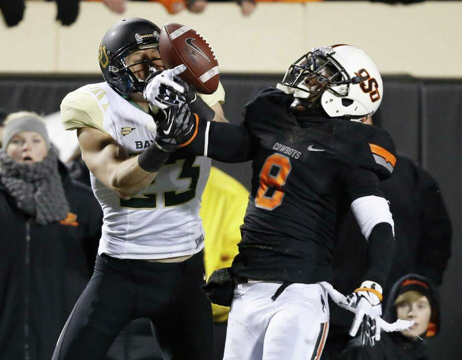 Oklahoma State safety Daytawion Lowe (right) breaks up a pass intended for Baylor wide receiver Clay Fuller, a former Smithson Valley standout, in the second quarter Saturday at Boone-Pickens Stadium in Stillwater, Okla.