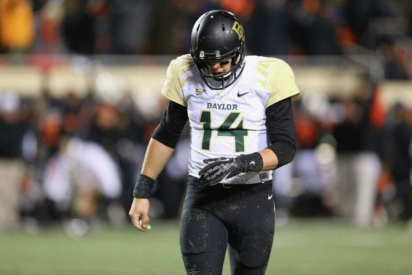 STILLWATER, OK - NOVEMBER 23: Bryce Petty #14 of the Baylor Bears walks off the field after Tyler Patmon #26 of the Oklahoma State Cowboys returned a fumble for a touchdown in the fourth quarter at Boone Pickens Stadium on November 23, 2013 in Stillwater, Oklahoma.