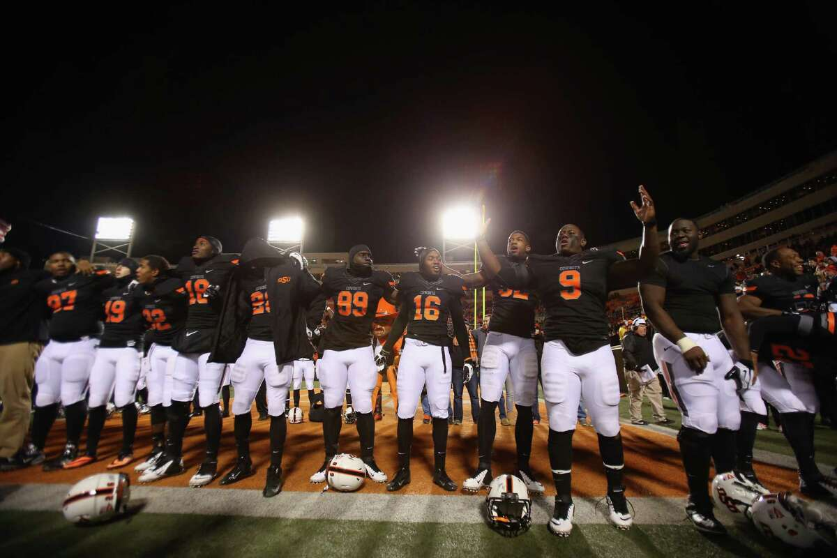 STILLWATER, OK - NOVEMBER 23: The Oklahoma State Cowboys celebrate a 49-17 win against the Baylor Bears at Boone Pickens Stadium on November 23, 2013 in Stillwater, Oklahoma.