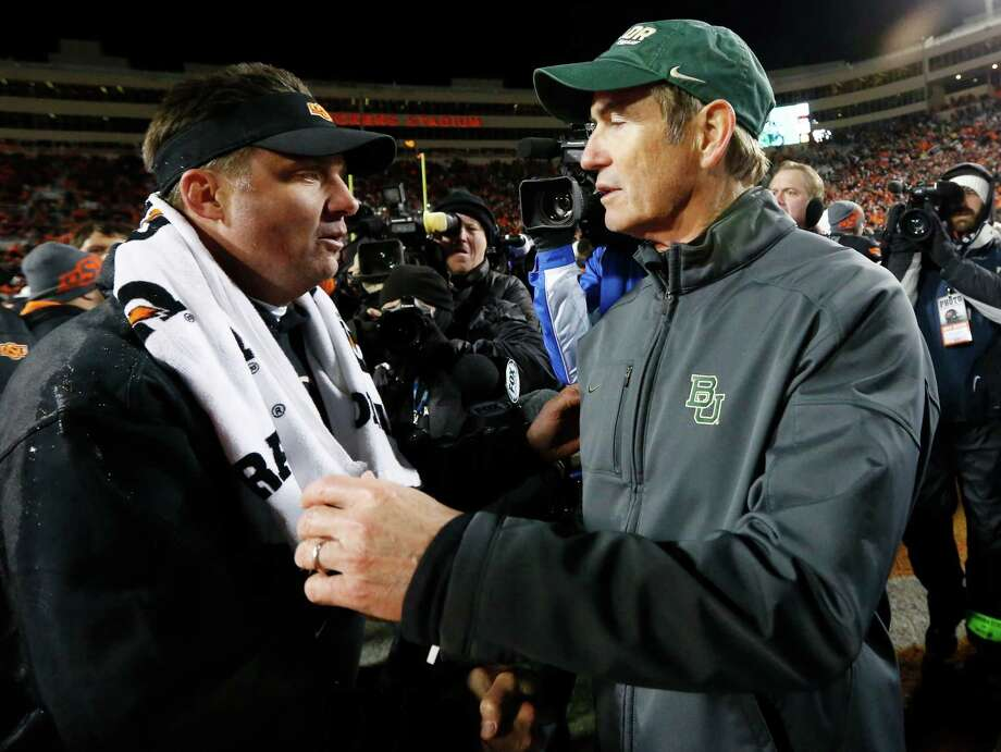 Oklahoma State head coach Mike Gundy, left, and Baylor head coach Art Briles, right, shake hands after their NCAA college football game in Stillwater, Okla., Saturday, Nov. 23, 2013. Oklahoma State won 49-17. (AP Photo/Sue Ogrocki) Photo: Sue Ogrocki, Associated Press / AP