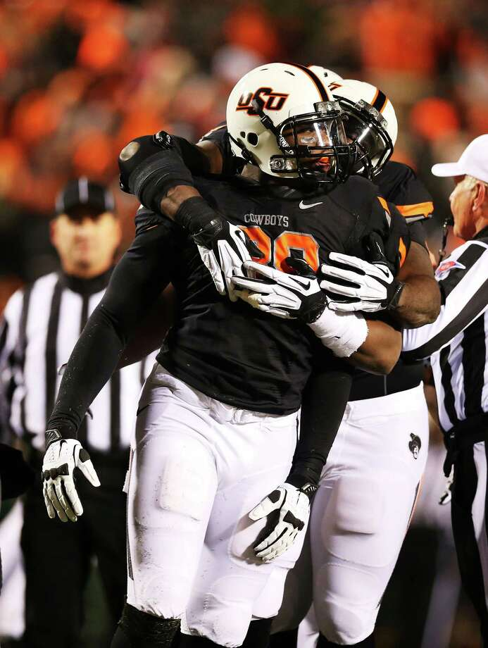 STILLWATER, OK - NOVEMBER 23:  Emmanuel Ogbah #38 of the Oklahoma State Cowboys celebrates with teammates in the second quarter against the Baylor Bears at Boone Pickens Stadium on November 23, 2013 in Stillwater, Oklahoma. Photo: Ronald Martinez, Getty Images / 2013 Getty Images