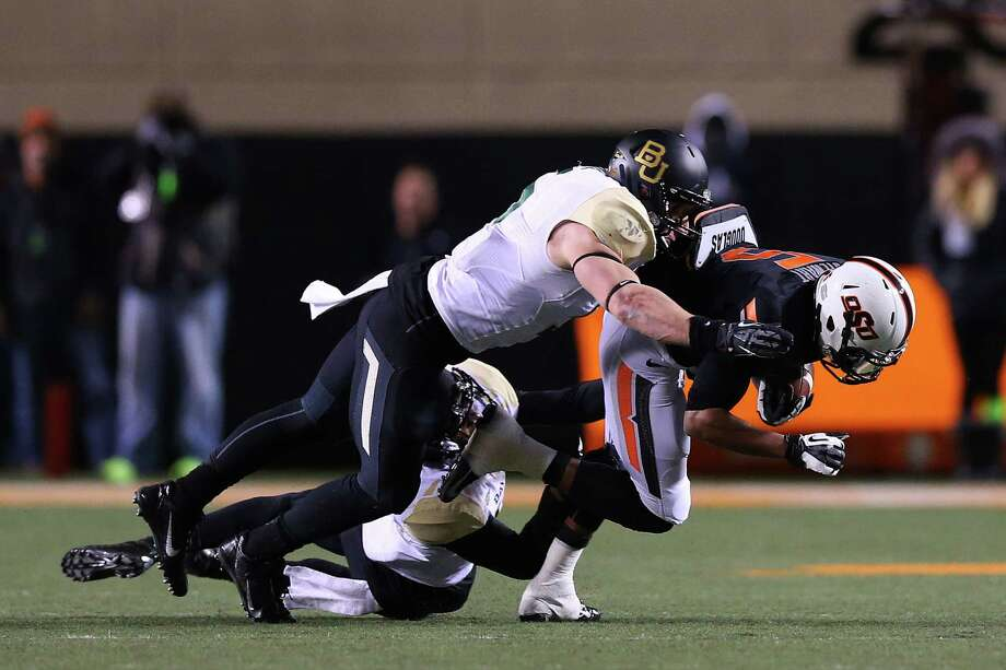 STILLWATER, OK - NOVEMBER 23:  Josh Stewart #5 of the Oklahoma State Cowboys is tackled by Terrell Burt #13 of the Baylor Bears in the second quarter at Boone Pickens Stadium on November 23, 2013 in Stillwater, Oklahoma. Photo: Ronald Martinez, Getty Images / 2013 Getty Images