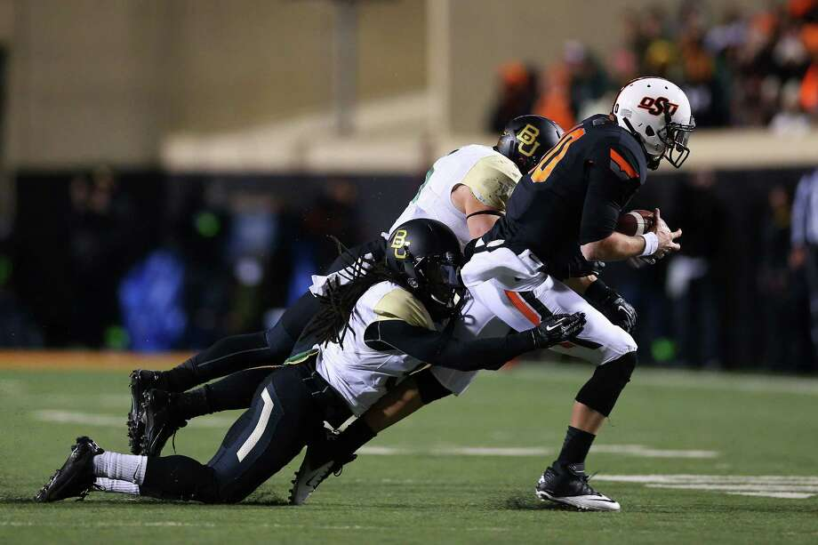 STILLWATER, OK - NOVEMBER 23:  Clint Chelf #10 of the Oklahoma State Cowboys is tackled by K.J. Morton #8 of the Baylor Bears in the second quarter at Boone Pickens Stadium on November 23, 2013 in Stillwater, Oklahoma. Photo: Ronald Martinez, Getty Images / 2013 Getty Images