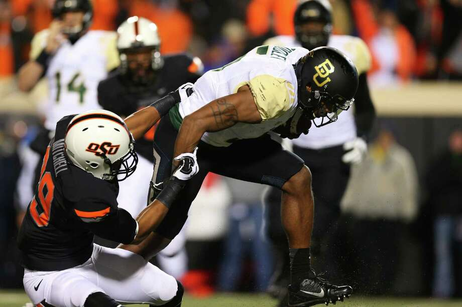 STILLWATER, OK - NOVEMBER 23:  Antwan Goodley #5 of the Baylor Bears carries the ball against Joe Mitchell #29 of the Oklahoma State Cowboys in the second quarter at Boone Pickens Stadium on November 23, 2013 in Stillwater, Oklahoma. Photo: Ronald Martinez, Getty Images / 2013 Getty Images
