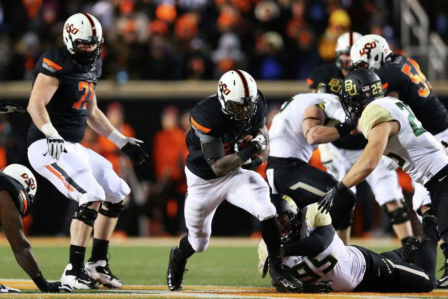 STILLWATER, OK - NOVEMBER 23:  Desmond Roland #26 of the Oklahoma State Cowboys carries the ball against the Baylor Bears in the second quarter at Boone Pickens Stadium on November 23, 2013 in Stillwater, Oklahoma. Photo: Ronald Martinez, Getty Images / 2013 Getty Images