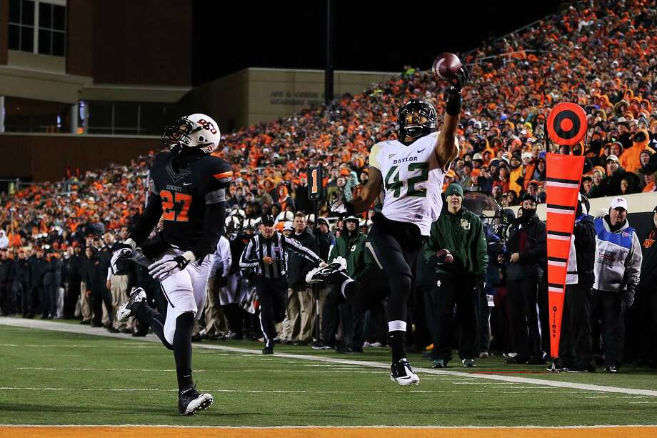 STILLWATER, OK - NOVEMBER 23:  Levi Norwood #42 of the Baylor Bears fails to complete a reception as Lyndell Johnson #27 of the Oklahoma State Cowboys defends in the second quarter at Boone Pickens Stadium on November 23, 2013 in Stillwater, Oklahoma. Photo: Ronald Martinez, Getty Images / 2013 Getty Images