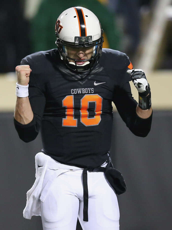 STILLWATER, OK - NOVEMBER 23:  Clint Chelf #10 of the Oklahoma State Cowboys celebrates a touchdown against the Baylor Bears in the third quarter at Boone Pickens Stadium on November 23, 2013 in Stillwater, Oklahoma. Photo: Ronald Martinez, Getty Images / 2013 Getty Images