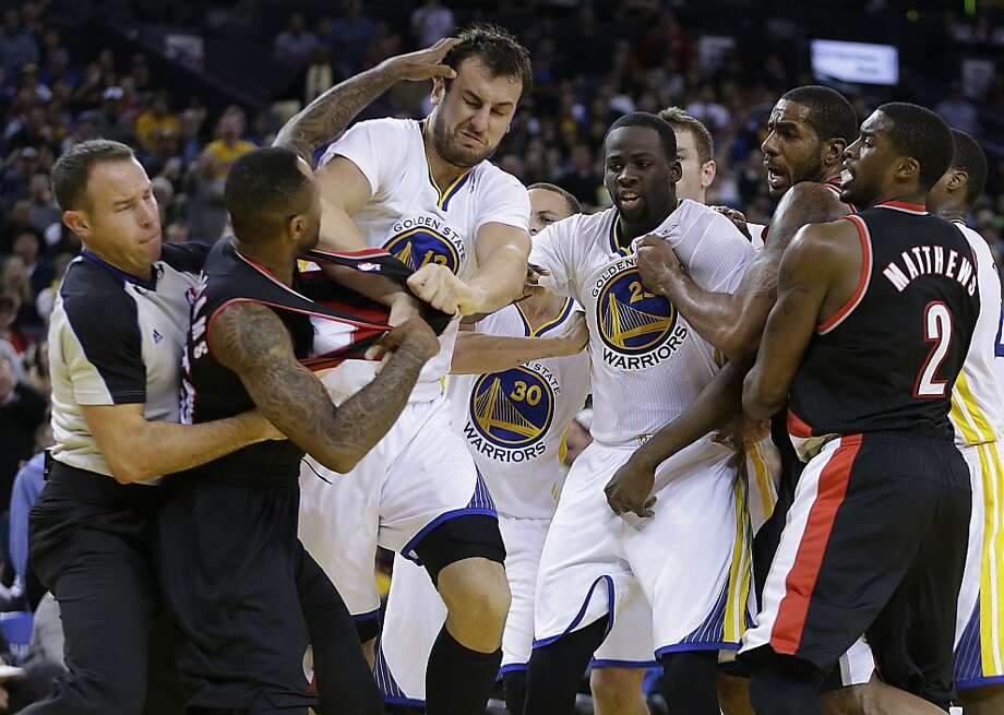 Mo Williams (left) is restrained by a referee while fighting with Andrew Bogut in the third quarter. Photo: Ben Margot, Associated Press