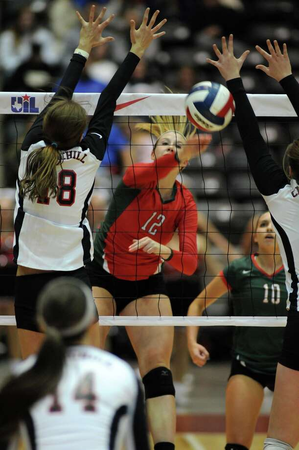 The Woodlands junior Rachel Reed, center, works the ball between two San Antonio Churchill defenders during their 2013 UIL Class 5A State Volleyball Championship match at the Culwell Center in Garland.