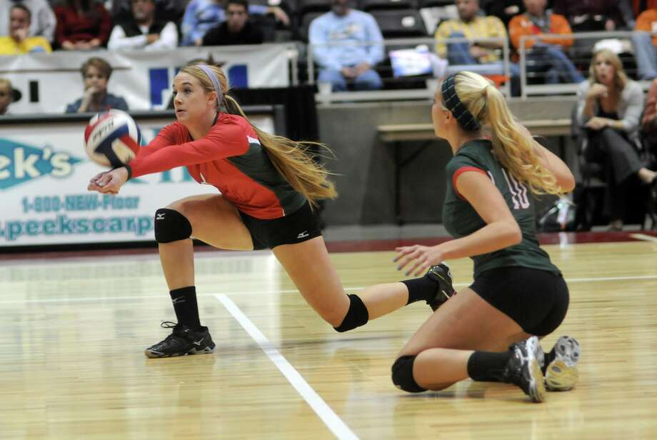 The Woodlands senior setter and Tournament MVP Courtney Eckenrode, left, digs the ball in front of teammate Kelly Quinn against San Antonio Churchill during their 2013 UIL Class 5A State Volleyball Championship match at the Culwell Center in Garland on Saturday.