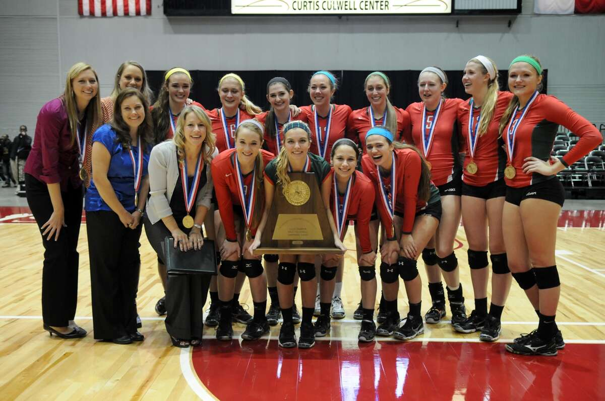 The Woodlands senior libero Kelly Quinn, center, and the 2013 UIL Class 5A State Volleyball Champions show off their trophy after defeating San Antonio Churchill in straight sets at the Culwell Center in Garland on Saturday.