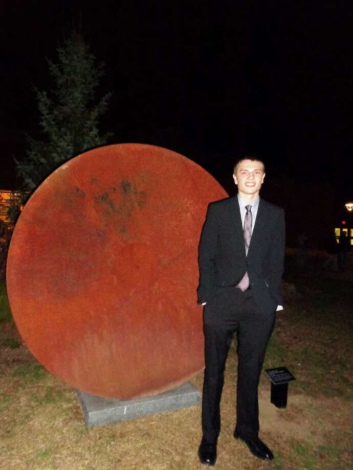 "Craig Logan, the 17-year-old grandson of Craig Matheson -- one of the two founders of the award-winning Staples Players -- stands next to a sculpture titled ""All the World's a Stage"" in a courtyard at Staples High School. The sculpture was dedicated Saturday in honor of Matheson and Steven Gilbert, the troupe's other founder. Photo: Meg Barone / Westport News contributed"