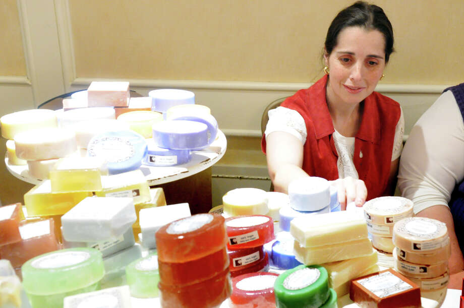 "Jennifer Joboulay works on the bath products display at the Abilis Gifts booth during the Junior League of Greenwich's Enchanted Forest annual fundraiser at the Hyatt Regency Greenwich in Greenwich, Conn., Nov. 24, 2013. This year's event featured a ""Celebration of Sweetness"" theme along with a visit from Santa and countless boutiques for holiday shopping. Photo: Keelin Daly / Stamford Advocate Freelance"