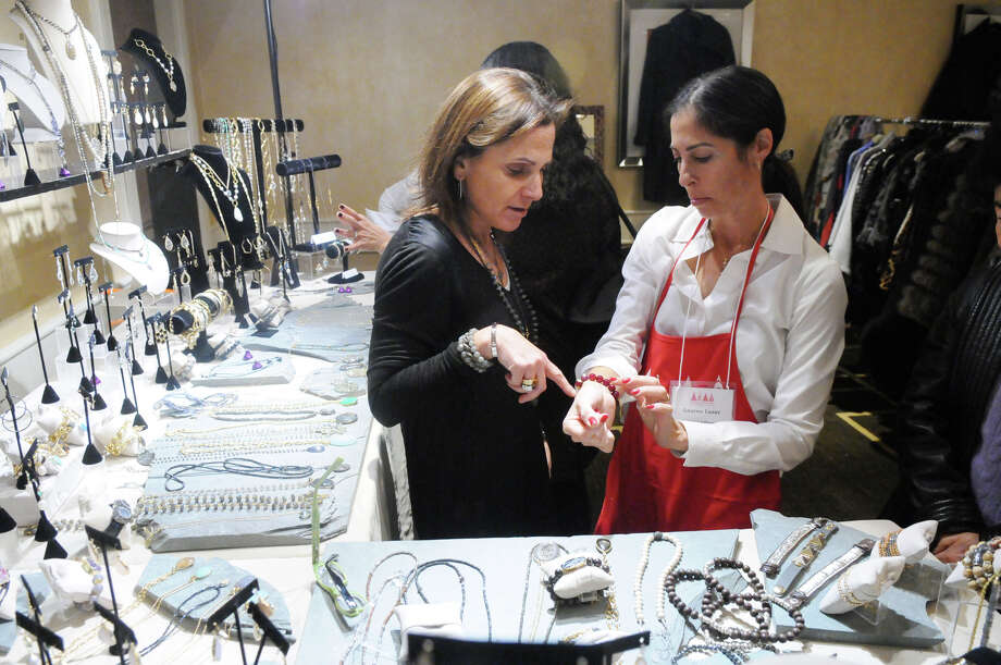 """Designer Ilyse Ennis helps customer Lauren Lazar as she hunts for jewelry in the Ilyse's Pieces boutique during the Junior League of Greenwich's Enchanted Forest annual fundraiser at the Hyatt Regency Greenwich in Greenwich, Conn., Nov. 24, 2013. This year's event featured a """"Celebration of Sweetness"""" theme along with a visit from Santa and countless boutiques for holiday shopping. Photo: Keelin Daly / Stamford Advocate Freelance"""