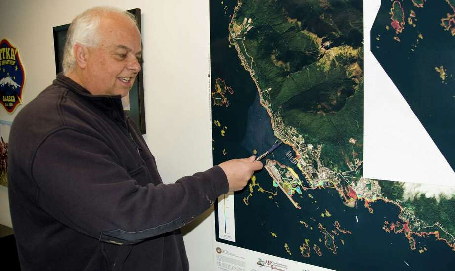 "Sitka Fire Dept. Chief Dave Miller points to areas on a just-published inundation map of Sitka, Alaska,  that would see the most damage in the event of a tsunami, Tuesday, Nov. 19, 2013,  at the Fire Hall.  The map from the state Department of Natural Resources Division of Geological and Geophysical Surveys shows the ""maximum estimated tsunami inundation"" with a red line that roughly borders the beach side of the HPR and Sawmill Creek Road road system and encompasses the downtown areas seaward of Lincoln Street and Katlian Street. Photo: JAMES POULSON, AP / Daily Sitka Sentinel"