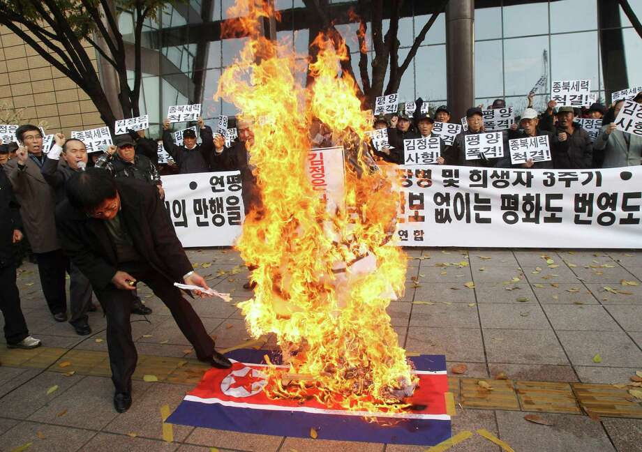 "A North Korean defector burns an effigy of North Korean leader Kim Jong Un and a North Korean flag during a rally to mark the the third anniversary of North Korea�s artillery attack on the Yeonpyeong island, in Seoul, South Korea, Saturday, Nov. 23, 2013. Four people, including two marines and two civilians, were killed by North Korea's attack. The banner read: ""Hang Kim Jong Un, Strike Pyongyang  and Get rid of pro-North ."" Photo: Ahn Young-joon, AP / AP"