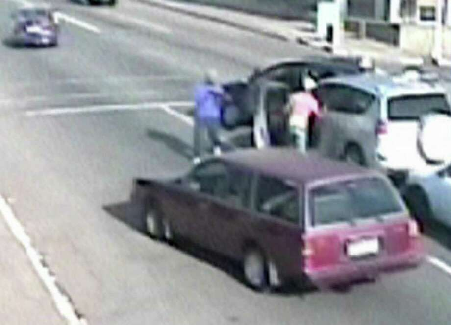 In this image taken from CCTV footage made available Friday Nov. 22, 2013, a dark coloured car in background blocks another car as an armed gang drag people from their car, during a carjacking, in Johannesburg, South Africa. A man wearing blue at centre brandishes a gun and another man pulls people from the car.  On three occasions this month, armed criminals who apparently knew their victims were carrying cash or valuables pounced at the same traffic intersection in Johannesburg while CCTV security cameras recorded the brazen heists. Photo: Uncredited, AP / AP2013