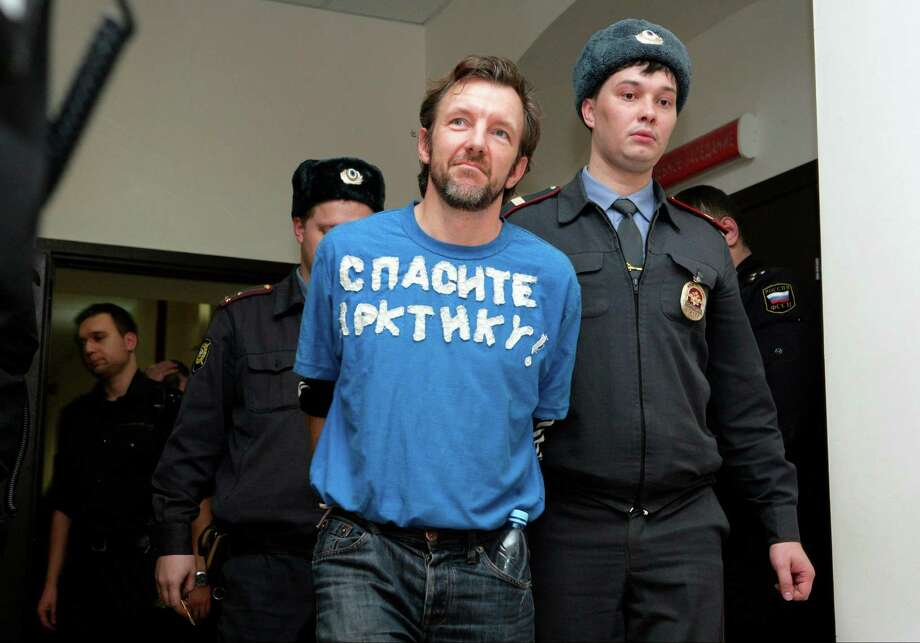 In this photo released by Greenpeace, Greenpeace International activist Philip Ball from the United Kingdom with 'Save The Arctic' sign on his T-shirt, is escorted in a court in St. Petersburg, Russia, Friday, Nov. 22, 2013, where Ball was granted bail. Russian judicial authorities are continuing to release Greenpeace activists on bail after they were arrested during an anti-oil drilling protest in Arctic waters two months ago. Photo: Igor Podgorny, AP / AP2013