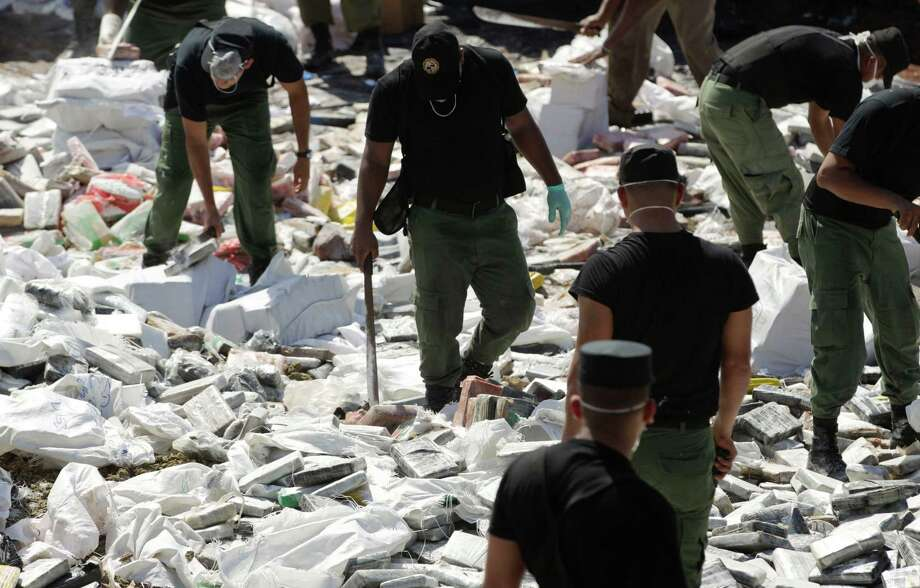 Police agents slash open seized packages of narcotics using machetes before burning them on the outskirts of Panama City, Friday, Nov. 22, 2013. According to police, they burned tons of seized cocaine, marijuana and heroin seized nationwide in the last three months. Photo: Arnulfo Franco, AP / AP