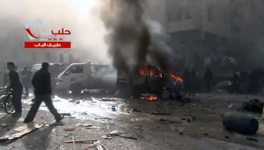 This image taken from a Saturday, Nov. 23, 2013, video obtained from the Sham News Network, which is consistent with independent AP reporting, shows burning vehicles and damage as a result of intense shelling by government forces in Aleppo, Syria. A string of government airstrikes on rebel-held areas in northern Syria killed  scores of people Saturday, activists said, as al-Qaida-linked rebels captured one of the country's major oil fields in the east. Photo: Uncredited, AP / AP2013