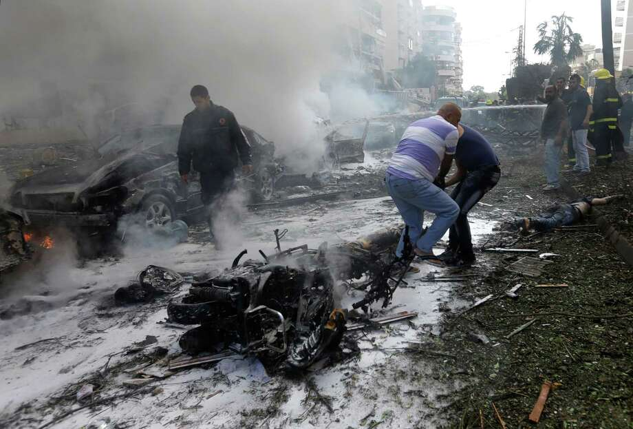Lebanese men remove a dead body from the ground in front of burned cars, at the scene where two explosions have struck near the Iranian Embassy killing many, in Beirut, Lebanon, Tuesday Nov. 19, 2013. The blasts in south Beirut's neighborhood of Janah also caused extensive damage on the nearby buildings and the Iranian mission. The area is a stronghold of the militant Hezbollah group, which is a main ally of Syrian President Bashar Assad in the civil war next door. It's not clear if the blasts are related to Syria's civil war. Photo: Hussein Malla, AP / AP2013