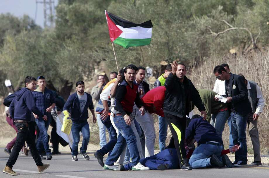 Palestinians gather around an injured man during clashes with Israeli security forces in the West Bank village of Yabed, near Jenin, Wednesday, Nov. 20, 2013. Clashes broke out as Palestinians protested the uprooting of their olive trees in the area. Photo: Mohammed Ballas, AP / AP2013