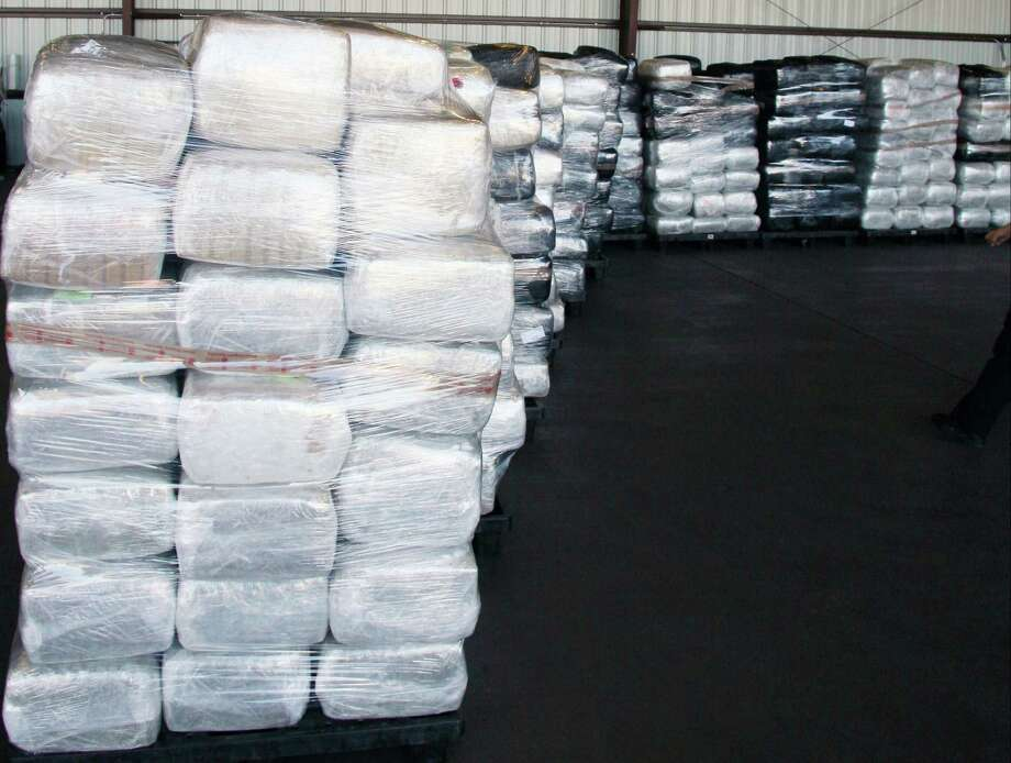 In a Nov. 2013 photo released by the U.S. Customs and Border Protection shows more than 20,000 pounds of marijuana hidden in a truckload of squash, captured as its driver tried to cross into the U.S. from Mexico. The tractor-trailer was passing through the Port of Nogales' Mariposa commercial facility last week when U.S. Customs and Border Protection officers pulled over the truck for further inspection. Officials uncovered 881 bundles of marijuana weighing 20,375 pounds and valued at more than $10 million, a record-breaking bust for Arizona, CBP said in a statement. Photo: AP / U.S. Customs and Border Protection