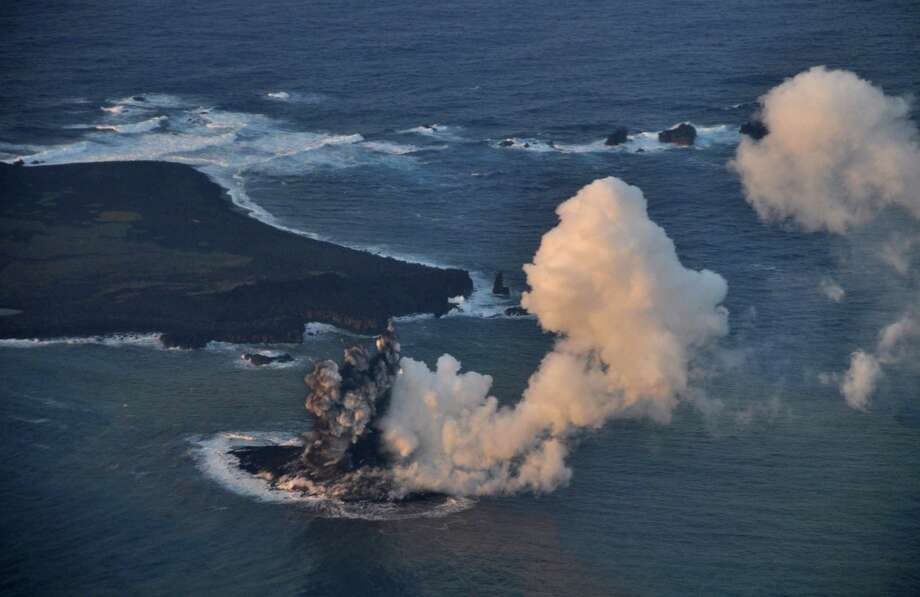 In this Wednesday, Nov. 20, 2013 photo released by Japan Coast Guard, smoke billows from a new island off the coast of Nishinoshima, seen left above, a small, uninhabited island in the Ogasawara chain, far south of Tokyo. The Japan Coast Guard and earthquake experts said a volcanic eruption has raised the new island in the seas to the far south of Tokyo. Photo: Uncredited, AP / AP2013