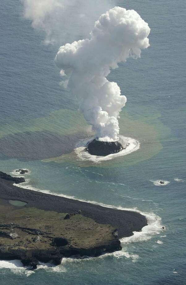 Smoke billows from a new island off the coast of Nishinoshima, seen at bottom, a small, uninhabited island in the Ogasawara chain, far south of Tokyo Thursday, Nov. 21, 2013. The Japan Coast Guard and earthquake experts said a volcanic eruption has raised the new island in the seas to the far south of Tokyo. The coast guard issued an advisory Wednesday warning of heavy black smoke from the eruption. (AP Photo/Kyodo News)  Photo: Uncredited, AP / AP2013