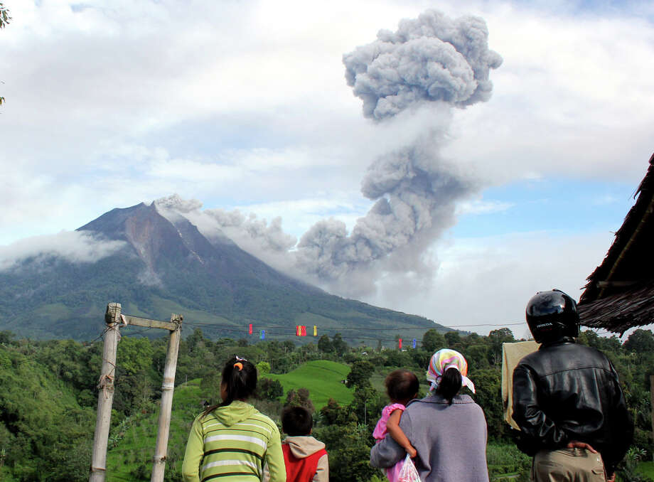 Villagers watch as Mount Sinabung sinabung spews volcanic material in Karo, North Sumatra, Indonesia, Sunday, Nov. 24, 2013. Officials raised the alert status of Sinabung to the highest level after a series of overnight eruptions. Photo: Dedy Zulkifli, AP / AP2013