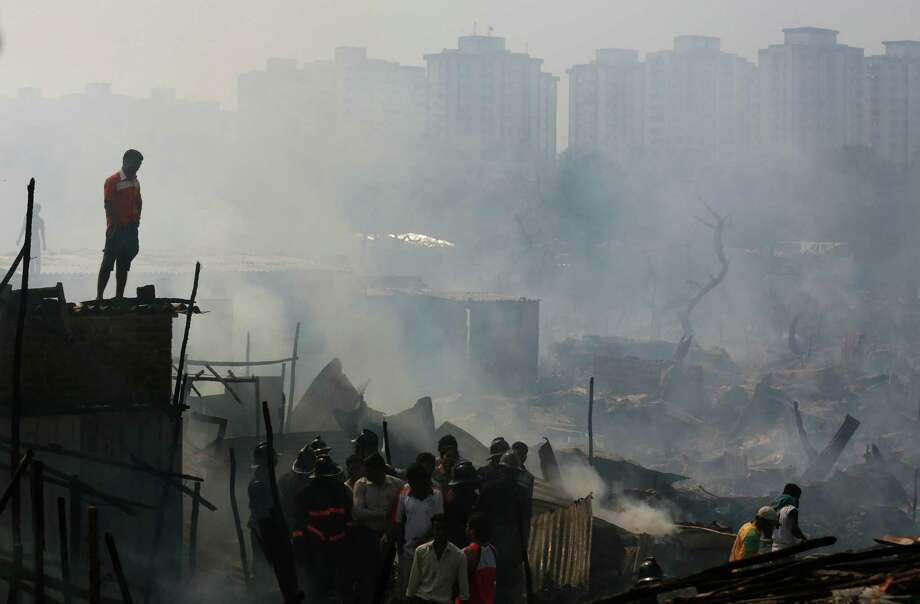 Residents watch as firefighters try to douse a fire at the Ambedkar Nagar slum in Mumbai, India, Thursday, Nov. 21, 2013. No injuries were reported and the cause of the fire was not known. Photo: Rafiq Maqbool, AP / AP