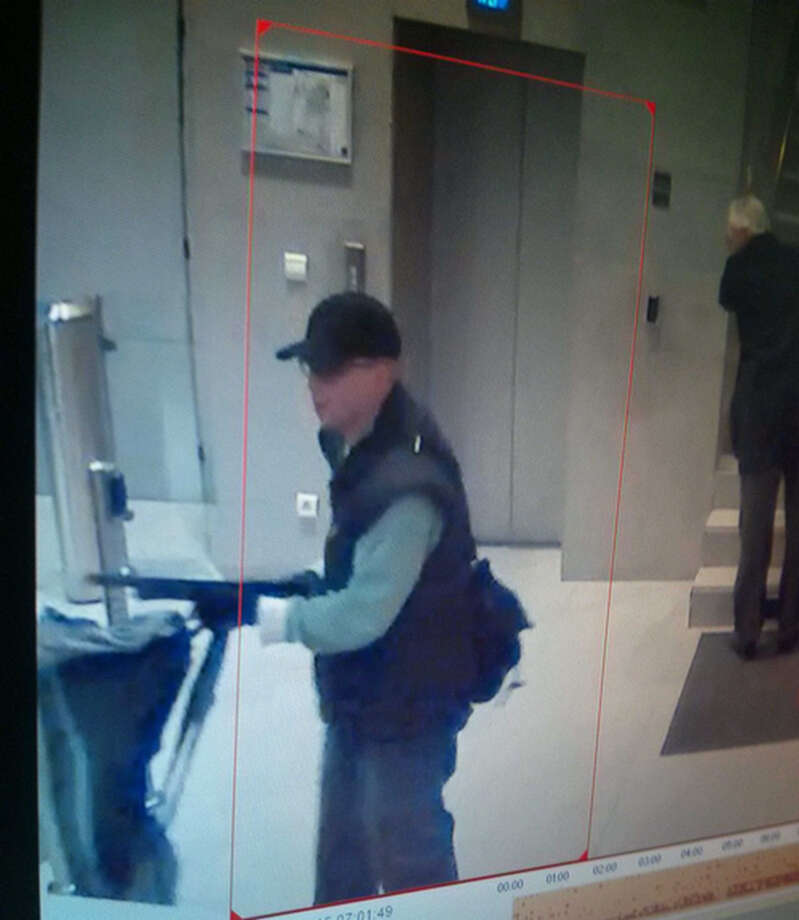 This photo taken from a footage of a security camera on Friday, Nov. 15, 2013, and released by the Paris Prefecture de Police, Monday, Nov. 18, 2013, shows a man pointing a shotgun at employees of the BFM TV station in Paris, France.The Paris prosecutor, Francis Molins, says a lone gunman appears to be behind a shooting at a Paris newspaper office that gravely wounded a photographer, and three other attacks. Monday's events happened three days after a gunman threatened journalists at the BFM-TV news network. Photo: Uncredited, AP / AP2013