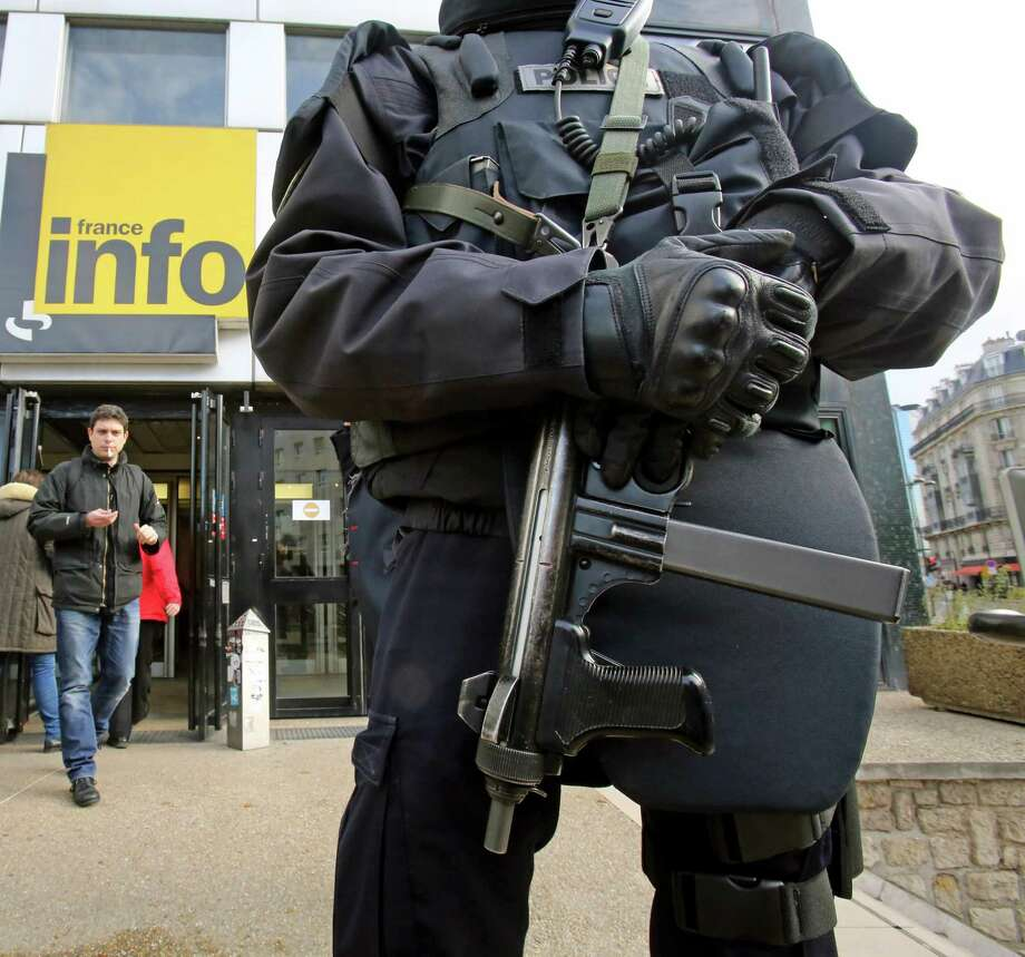 A French police officer wearing a bullet-proof jacket stands at the entrance of France Info radio station in Paris, Tuesday Nov. 19, 2013. A French police are hunting for a gunman suspected in a shooting Monday at a Paris newspaper office that gravely wounded a photographer, as well as three other attacks around the nation's capital. The motive for the attacks, which prompted heightened security at media offices and the busy Champs-Elysees shopping avenue, is unclear. Photo: Remy De La Mauviniere, AP / AP2013