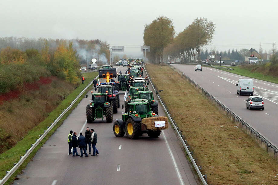 French farmers stand next to their tractors on a highway converging on Paris slowing traffic to a crawl in the second low speed protest in Orgeval, west of Paris, Thursday Nov. 21, 2013. The French president's popularity edges lower by the week, dragged down by a sluggish economy that is eroding peoples faith and their willingness to pay some of the highest taxes. Photo: Francois Mori, AP / AP