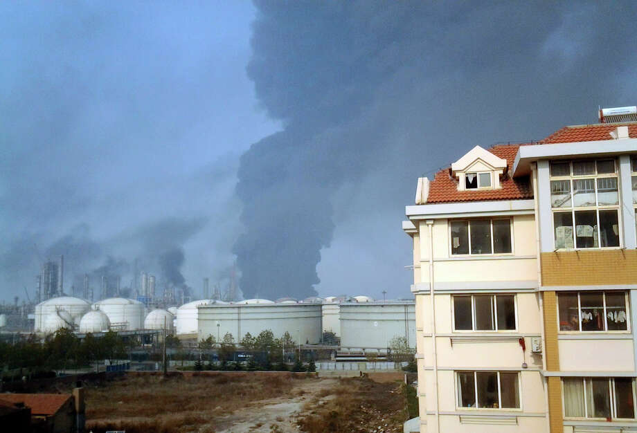 Smoke rises from oil refineries after explosion in Qingdao in east China's Shandong province, Friday, Nov. 22, 2013. The oil pipeline owned by China's largest oil refiner, Sinopec, ruptured and while being repaired caught fire and exploded, killing many people and injuring others, a district government in the port city of Qingdao said. (AP Photo)  Photo: AP / CHINATOPIX