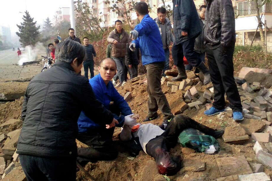 People attend an injured man after a pipeline explosion in Qingdao in east China's Shandong province Friday, Nov. 22, 2013. Leaked oil from a ruptured oil pipe, owned by China's largest oil refiner, Sinopec, caught fire and exploded Friday in an eastern Chinese port city, killing and injuring many people. (AP Photo)  Photo: AP / CHINATOPIX