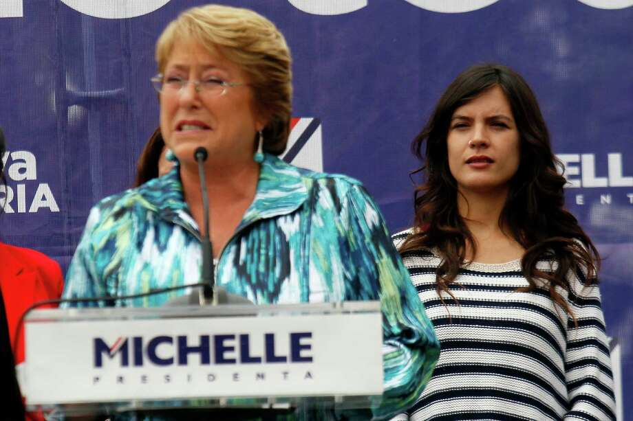 Chile's presidential candidate Michelle Bachelet speaks at a campaign rally in Santiago, Chile, Tuesday, Nov. 19, 2013. Pictured right is newly elected member of Congress and former student leader Camila Vallejo of the Communist Party. Photo: Luis Hidalgo, AP / AP
