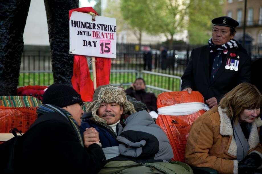 Gyanraj Rai, center, aged 55, a retired Gurkha warrant officer from the British military takes part in the 15th-day of his hunger strike opposite the entrance to Downing Street in London, Thursday, Nov. 21, 2013. His hunger strike is in demand of equal pension rights in line with the rest of the military as many Gurkhas who retired before 1997 get about a third of the pension received by British former soldiers. Photo: Matt Dunham, AP / AP