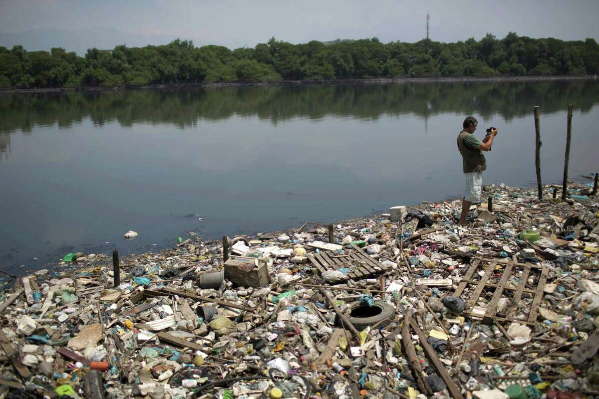 In this Oct. 23, 2013 photo, biologist Mario Moscatelli takes photographs from trash floating on the polluted waters of the Canal do Fundao in Rio de Janeiro, Brazil. Moscatelli, who oversees the reforestation of mangrove forests along the bay, said he fears that even if the bay is cleaned up, the state will let it deteriorate after all the athletes have gone home. Rio de Janeiro will host the 2016 Olympic Games.