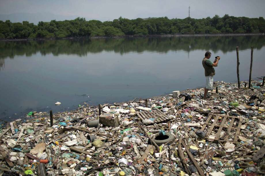 In this Oct. 23, 2013 photo, biologist Mario Moscatelli takes photographs from trash floating on the polluted waters of the Canal do Fundao in Rio de Janeiro, Brazil. Moscatelli, who oversees the reforestation of mangrove forests along the bay, said he fears that even if the bay is cleaned up, the state will let it deteriorate after all the athletes have gone home. Rio de Janeiro will host the 2016 Olympic Games. Photo: Felipe Dana, AP / AP2013