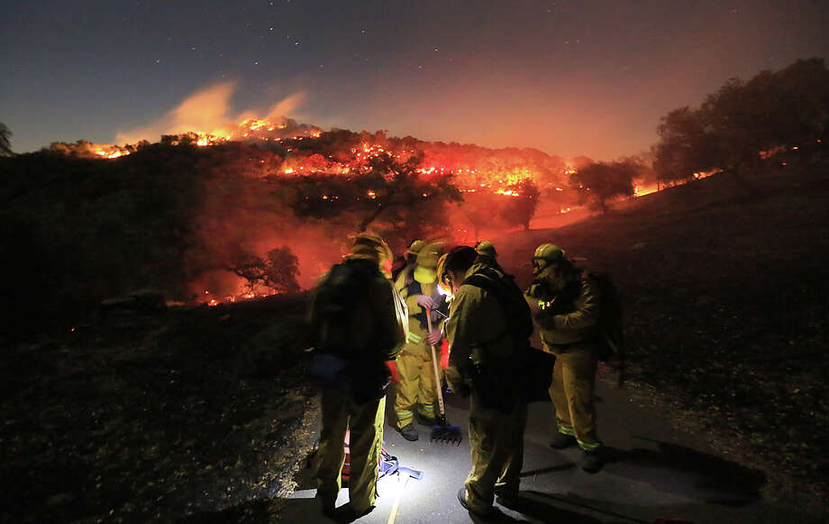 Firefighters from Schell Vista of Sonoma County and Santa Clara County Cal Fire prepare to put out hotspots on a fire in the hills of Soda Canyon above Napa, Calif., Friday, Nov. 22, 2013.  The fire grew to over 300 acres by daybreak, fanned by high winds. Photo: Kent Porter, AP / AP2013