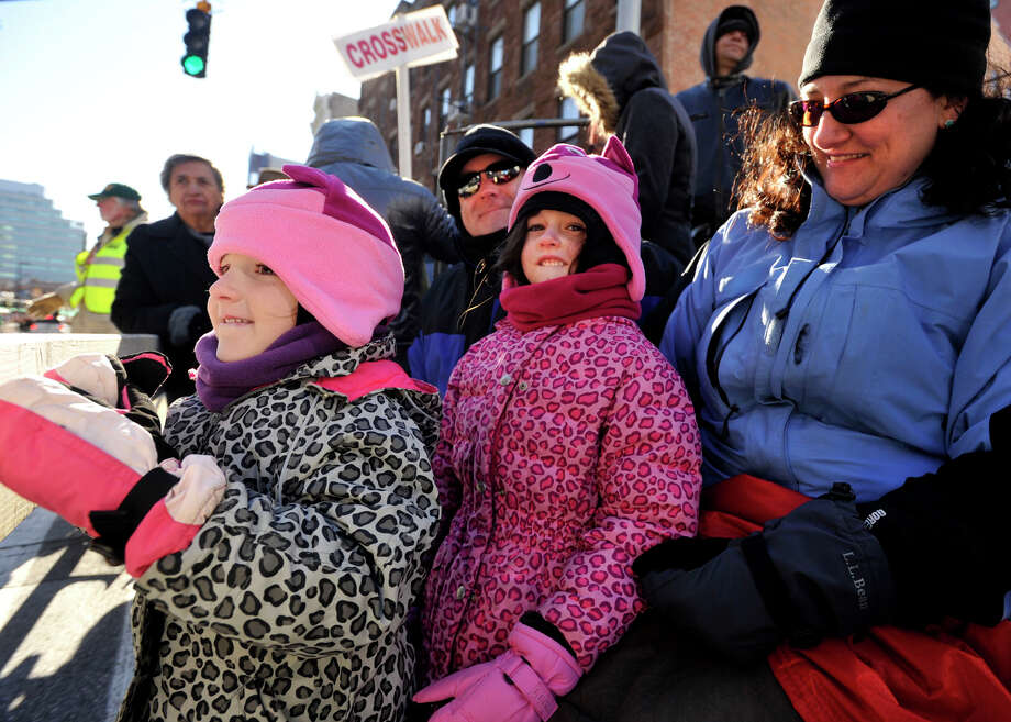 Cassidy O'Brien, left, and her sister, Caitlin, watch the parade with their parents Irene, right, and Kevin O'Brien during the UBS Parade Spectacular in downtown Stamford, Conn., on Sunday, Nov. 24, 2013. Photo: Jason Rearick / Stamford Advocate