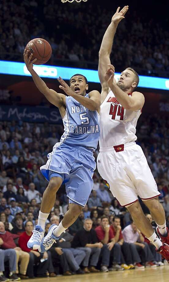 North Carolina's Marcus Paige, who had 32, points, drives to the basket against Louisville's Stephan Van Treese. Photo: Robert Willett, McClatchy-Tribune News Service