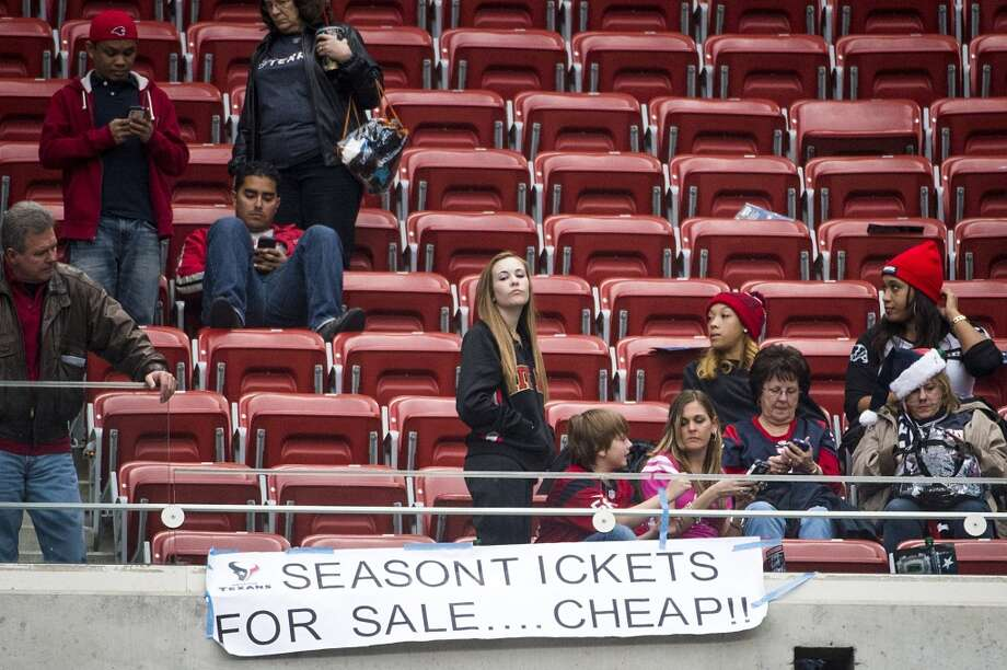 "Texans fans stand over a sign reading ""Season Tickets For Sale....Cheap!!"" following a loss to the Jacksonville Jaguars on Nov. 24. Photo: Smiley N. Pool, Houston Chronicle"