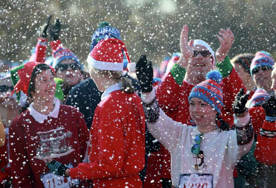 Fake snow is blown on participants during the Ugly Sweater Run on Sunday, Nov. 24, 2013, at Magnuson Park in Seattle. The 5K run benefited Toys For Tots as each participant donated a new toy to the foundation. Photo: SOFIA JARAMILLO, SEATTLEPI.COM / SEATTLEPI.COM
