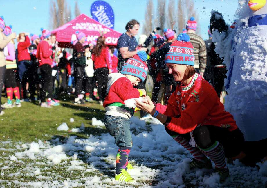 Oliver Monton and Lisa Farmer play in fake snow during the Ugly Sweater Run on Sunday, Nov. 24, 2013, at Magnuson Park in Seattle. The 5K run benefited Toys For Tots as each participant donated a new toy to the foundation. Photo: SOFIA JARAMILLO, SEATTLEPI.COM / SEATTLEPI.COM